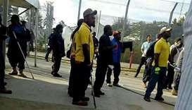 Papua New Guinean police officers enter the Manus Island immigration detention centre