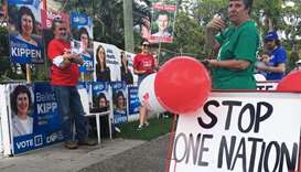 "Voters stand by a ""stop One Nation - vote Labor"" sign in Graceville, near Brisbane"