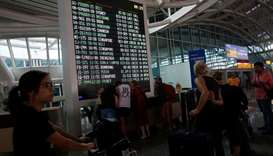 Passengers stand near the flight information board at Ngurah Rai International airpot in Bali