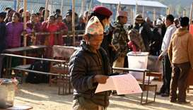 A Nepali voter examines a ballot papers before casting his vote at a polling station during the gene