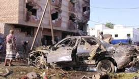 Man stands by a damaged car at the site of a car bomb attack outside the Finance Ministry offices in