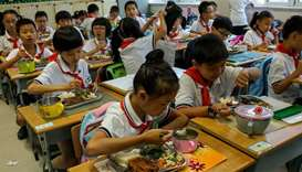 Students eat their lunch during the lunch break at their school in Shanghai