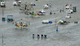 People walk through a flooded area of Marina Beach after heavy rains in Chennai