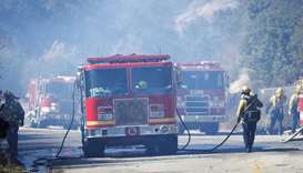 Firefighters work on hoses next to fire trucks as they battle the Woolsey fire in West Hills