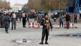 Afghan policemen keep watch at the site of a blast in Kabul