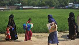 Rohingya refugees walk with belongings in Jamtoli refugee camp near Ukhia in Bangladesh