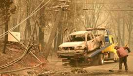 Crews begin removing vehicles from the streets after the Camp fire tore through the area in Paradise