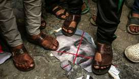 Palestinian demonstrators step on a burnt image of Israeli Defence Minister Avigdor Lieberman