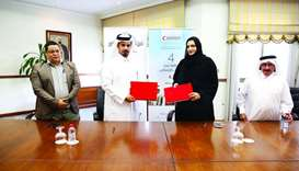 QRCS and Al-Jasrah Club officials at the MoU-signing ceremony.