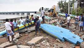 Indian people look at debris of boats in Velankanni in India's southern Tamil Nadu state