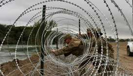 Soldiers from the Kentucky-based 19th Engineer Battalion are installing barbed wire fences on the ba