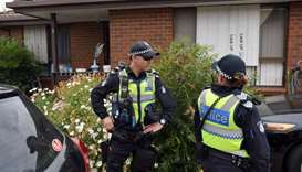 Police stand guard outside a house raided by police in the Melbourne suburb of Dallas
