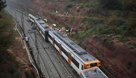 Rescue workers survey the scene after a commuter train derailed between Terrassa and Manresa, outsid
