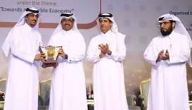 HE Dr Mohamed bin Saleh al-Sada receiving a token of recognition from engineer Abdullatif Ali al-Yaf
