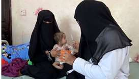 A Yemeni mother holds her malnourished child as a nurse tries to feed the baby at Al-Mudhafar hospit
