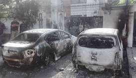 Pakistani security personnel stand next to burned out vehicles in front of the Chinese consulate aft