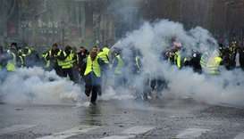 Yellow vests (Gilets jaunes) protestors demonstrate amid tear gas on the Champs Elysees in Paris