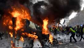 A man throws a bike in a burning truck during a protest of Yellow vests  in Paris