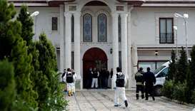 Turkish police forensic experts and plainclothes police officers stand at the entrance of a villa in