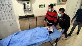 A woman lies on a stretcher inside a hospital after what the Syrian state media said was a suspected