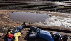 Migrants sleep next to railway tracks near the town of Bujanovac, Serbia