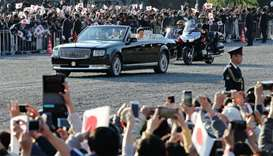 People cheer as the motorcade of Japan's Emperor Naruhito and Empress Masako leaves the Imperial Pal