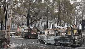 The burnt-out remains of cars and property belonging to Art Murphy and his wife Shirley are seen fol