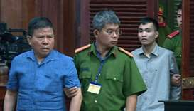 Police escort Chau Van Kham (L) and Tran Van Quyen (R) to their trial at a court in Ho Chi Minh city