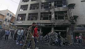 Security members and firefighters gather the site of an explosion in the Syrian Kurdish-majority cit