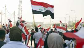 Iraqi medical students wave the national flag as they take part in ongoing anti-government protests