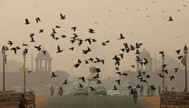Birds fly as people commute near India's Presidential Palace on a smoggy day in New Delhi, India