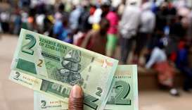 A man poses with Zimbabwe's new two dollar banknotes as customers queue outside a bank in Harare