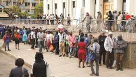 People queue to withdraw money from a bank in Harare yesterday.