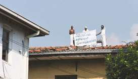 Prisoners display a banner on the roof of a building inside the Welikada prison in Colombo yesterday
