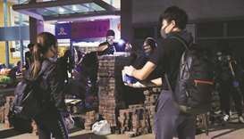Anti-government protesters build a brick wall as a roadblock during a hold-up against the police at