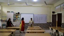 Teachers talk to each other in an empty classroom of a school after it remained closed on account of