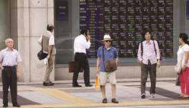 Pedestrians wait to cross a road in front of an electronic stock board outside a securities firm in
