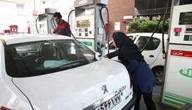 A women fills up her car's tank at a petrol station, after fuel price increased in Tehran