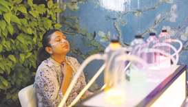 A woman breathes in oxygen mixed with aromatherapy via a nasal cannula, at an oxygen bar in New Delh