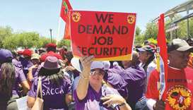 South African Airways workers hold placards during a strike over wages at SAA headquarters in Johann