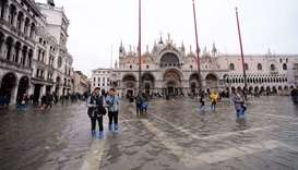 Tourists walks in St. Mark square on November 16, 2019 in Venice, three days after the city suffered