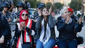 Demonstrators gesture near Lebanese police during the ongoing anti-government protest, in Beirut