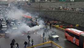 Riot police tries to disperse people on Saturday as they protest on a highway against increased gas