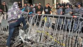 A Lebanese protester steps on a metal barrier through a barbed wire fence before security forces nea