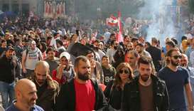 Smoke rises as demonstrators walk during the ongoing anti-government protest, in Beirut