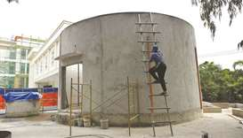 A worker climbs on the concrete entrance of the El Deposito, a Spanish-era water reservoir being reh