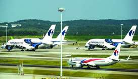 A Boeing Co 737-800 aircraft, operated by Malaysian Airlines, stands in front of Airbus SE A380 airc