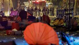 Police officers stand guard in front of a street scattered with umbrellas outside Hong Kong Polytech