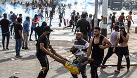 Iraqi protesters carry away an injured comrade amid clashes with riot police during a demonstration