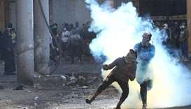 An Iraqi demonstrator throws away a tear gas canister during the ongoing anti-government protests in
